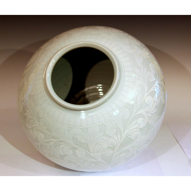 Large Korean studio porcelain moon vase with carved slipware design of a peony scroll. hand-turned and hand decorated....