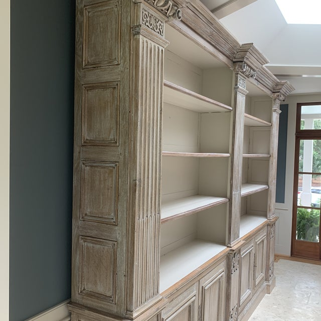 Grand Antique oak French castle bookcase, doors below and open above. Pilasters are surmounted by carved Corinthian...