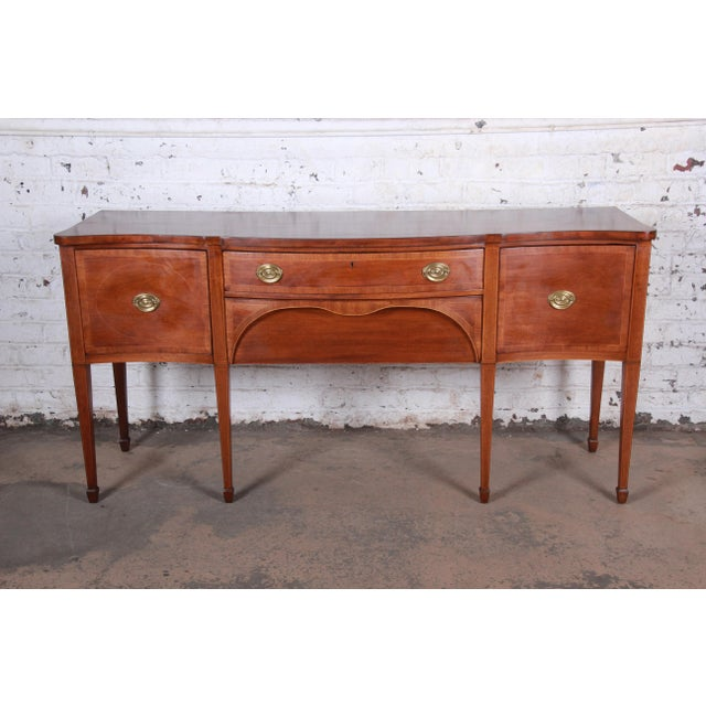An inlaid mahogany sideboard credenza Made by Kittinger Furniture Company USA, Circa 1950s Mahogany + brass Measures:...