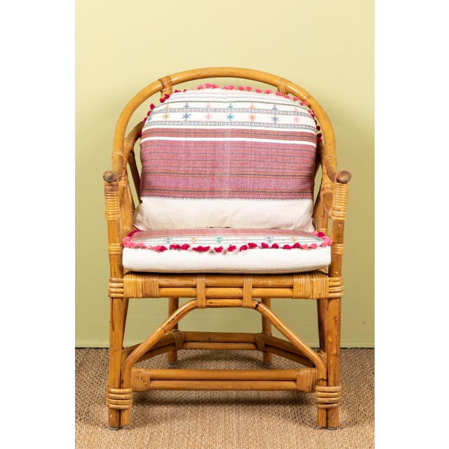 Vintage rattan chair with cushions made of Injiri organic cotton textiles from India. Textile has areas of hand embroidery...