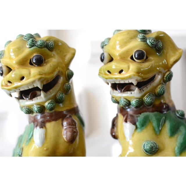 This listing is for a pair of 1940s vintage, Chinese Foo Dog ceramic statues. The color is a chartreuse yellow with lime...