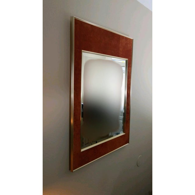 An elegant double framed beveled mirror with burnt orange suede paneling between the interior and exterior frame.