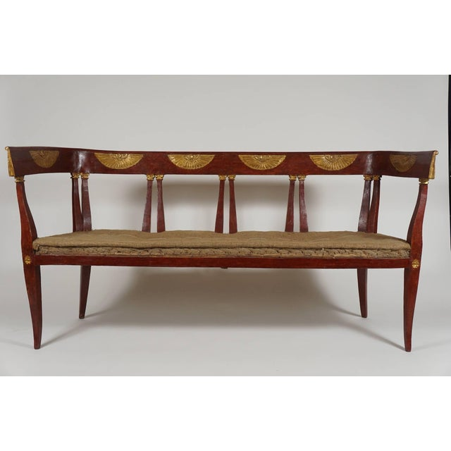 An exquisite, circa 1805, Italian 'Egyptian' style parcel gilt and painted settee having klismos form crest rail with gilt...