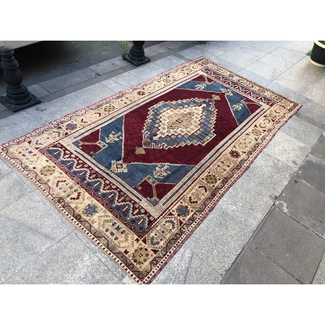 This is a vintage Turkish Oushak rug from the 1960s. The piece was hand-knotted.