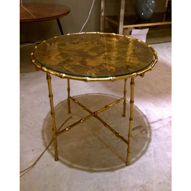 Mid Century Modern French faux bamboo coffee table, in brass. The round table top is acid treated brass, covered by a...
