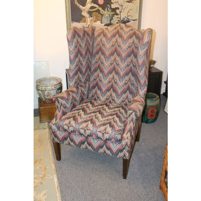 Reproduction colonial flame stitch style upholstered wing chair in hues of purple and blue on wooden legs.