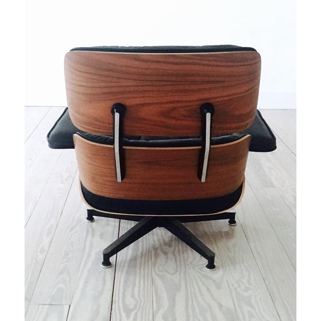 An iconic piece of modern furniture, this Third Generation Eames Lounge Chair and Ottoman in Black Leather and a Walnut...
