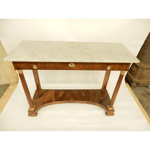 Early 19th century walnut French Empire console with white marble top. It has one draw the with of the console and one...
