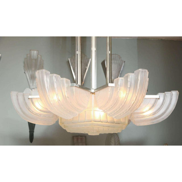 Marius Ernest Sabino. Art Deco chandelier, circa 1930, comprised of six clear and frosted glass shades radiating from a...