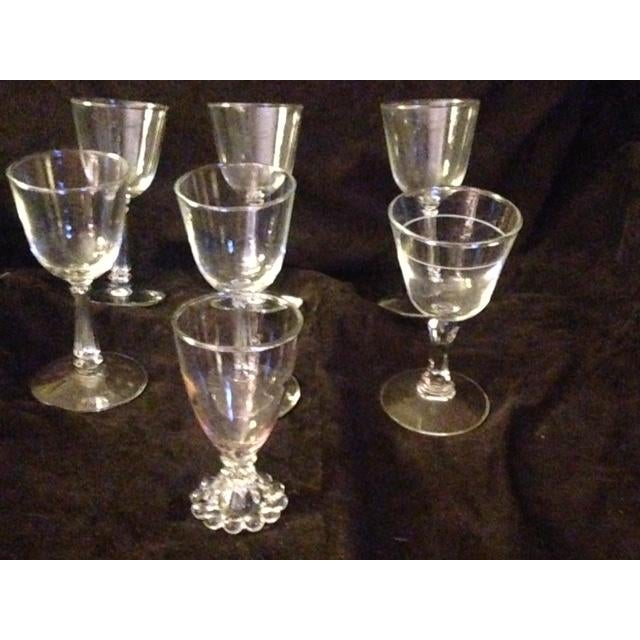 This is a set of 7 vintage wine glasses. 5 are identical. There is one wine glass with a balled ring around it. One glass...