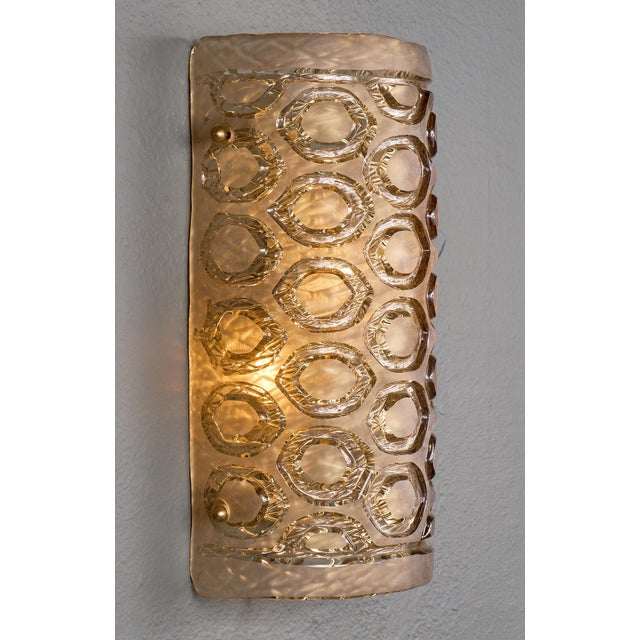 A pair of Murano glass sconces of frosted glass with a geometric stamped pattern. We love the size and dynamic curve of...
