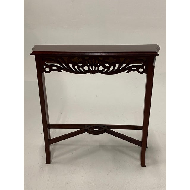A cute sized mahogany console having lovely fret work apron on front and sides and a nicely designed stretcher beneath.
