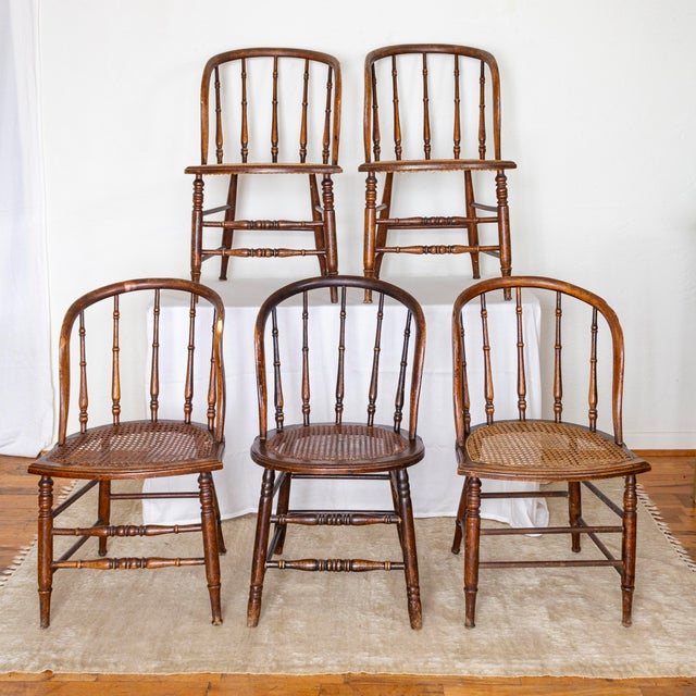 Primitive bow back chairs feature crest shaped, cane seats, spindle backs, turned legs and stretchers, and a rich patina...