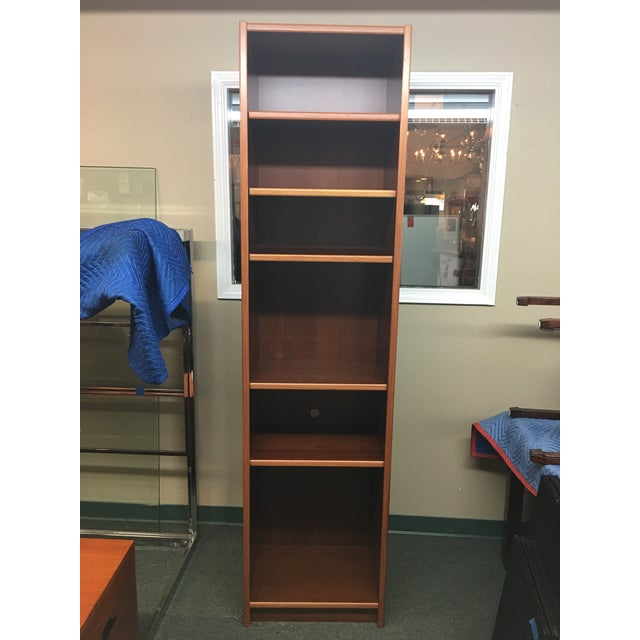 Design Plus Consignment Gallery presents a stylish storage solution. Narrow and tall, the teak veneer bookcase offers lots...