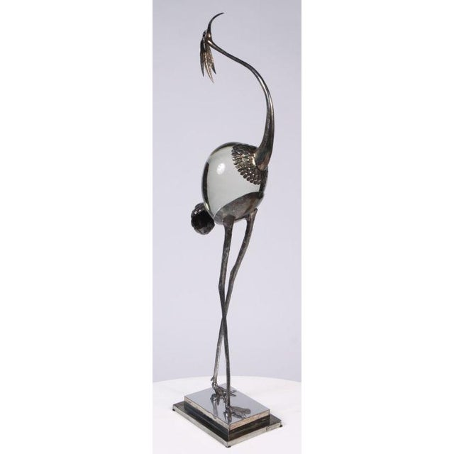 A graceful sculpture of a slender crane, its body is a large smooth crystal and its head, neck and legs are in silver...