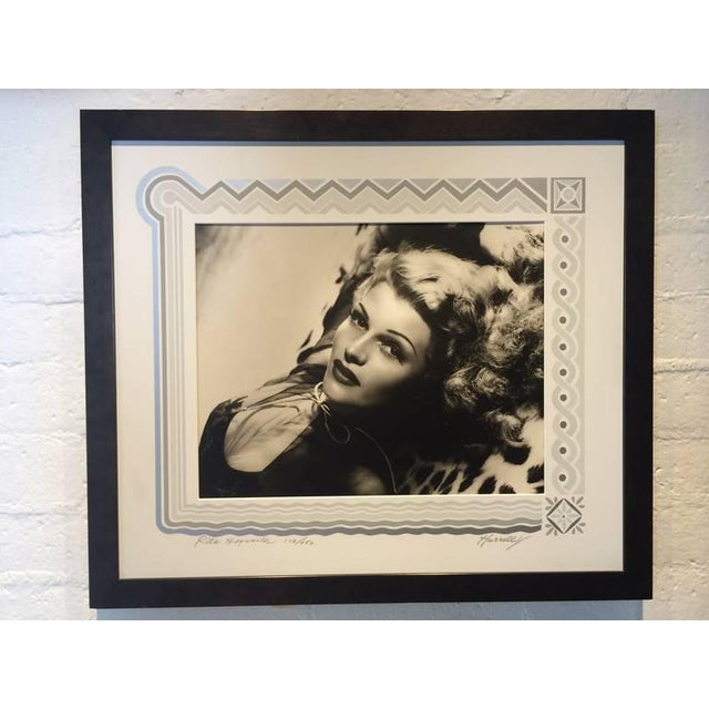 This is a signed black and white photograph of Rita Hayward numbered 102/450 taken in 1944. The serigraph art deco border...