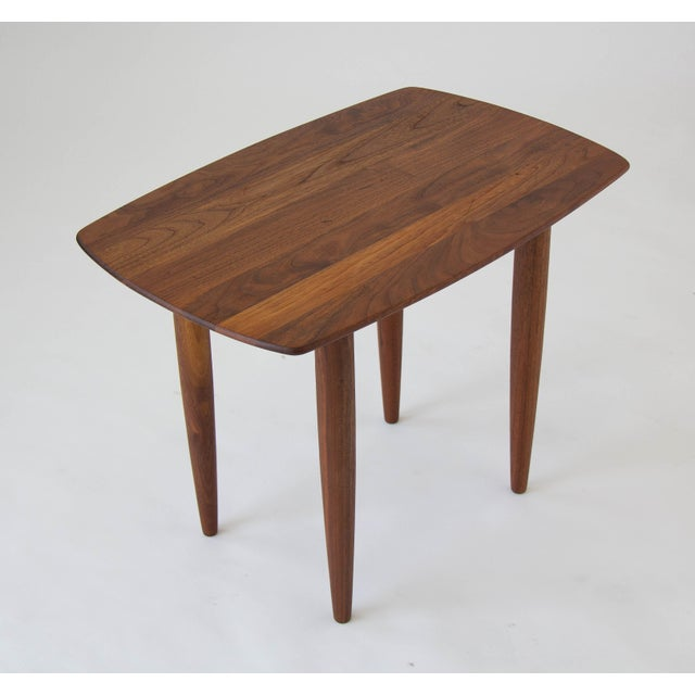 A tall side table with a rounded rectangular tabletop from California-based manufacturer Prelude. The table is solid...