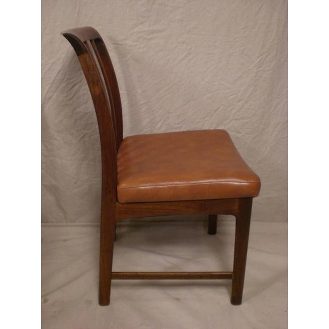 Mid-Century Modern dining chairs by DUX with rosewood frames and orange vinyl seating. Seat backs have a nice curve to...