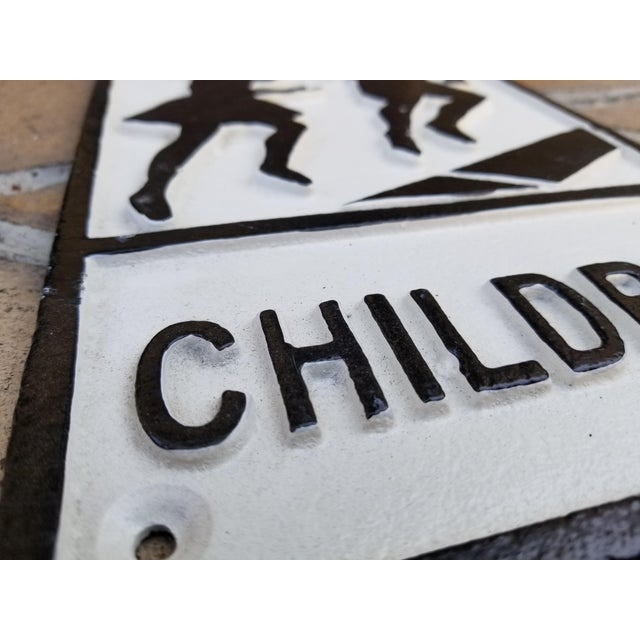A cast iron sign depicting children. Used as a street warning sign. England. Raised design and lettering