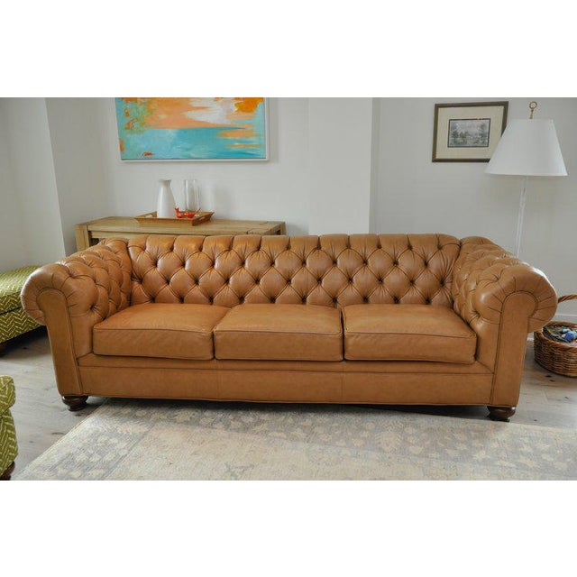Ethan Allen leather sofa is a tufted, chesterfield style with three seat cushions in a warm, rich caramel color. The light...