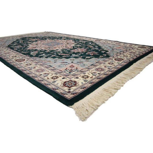 This hand-knotted wool vintage Persian style rug features a traditional Tabriz design in a rectilinear style. A lozenge...