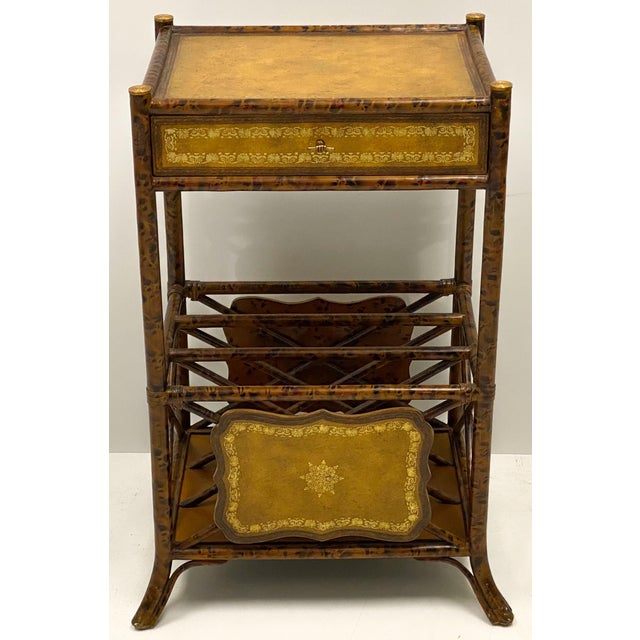 This is a Maitland-Smith side table with faux tortoise finished bamboo frame and tooled leather surfaces. It has a...