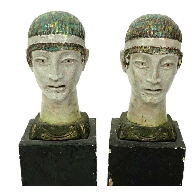 A pair of Mid Century Glazed Faience Pottery Figural Busts on wood stands. These unique one of a kind pieces are possibly...