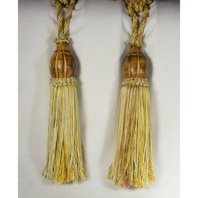 Braided rope tie backs with a carved wood cap atop a seven and a half inch fabric tassel. Multi color shades of gold,...