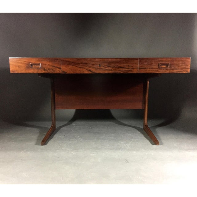 """Purchased in Denmark, this sleek """"Cassette-form"""" desk is in a gorgeous Rosewood from the 1970s. It is attributed to Georg..."""