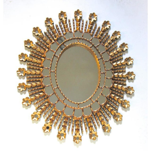 Hand-carved giltwood sunburst oval shaped wall mirror. Two rows of small inset mirrors encircle the large central mirror...