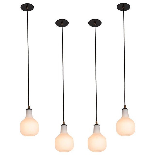 1950s Italian glass pendants attributed to Stilnovo. Executed in opaline matte glass, brass and black painted metal. These...