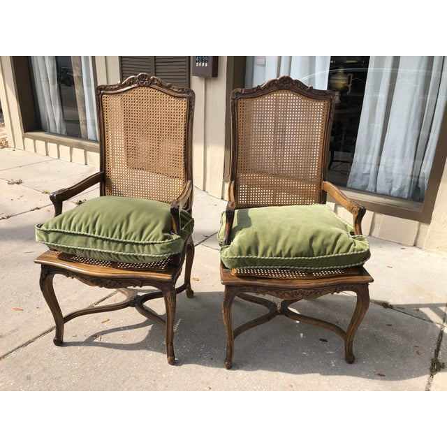 Pair of French caned chairs with newer cane back and seat. Frames have a lovely warm patina and classic French carvings....