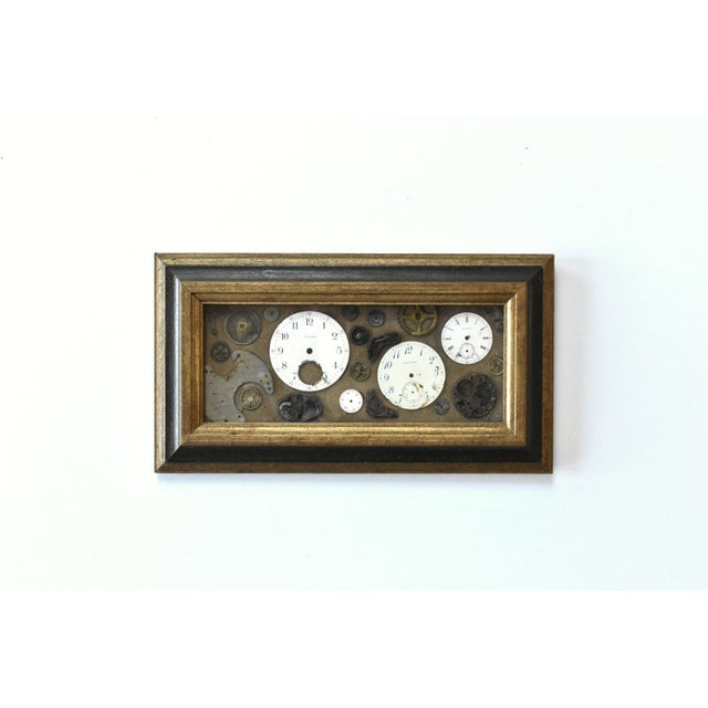 A vintage, mid-century framed art piece of collage pocket watch pieces by Lee Waterman. In a black and old gold wood frame.