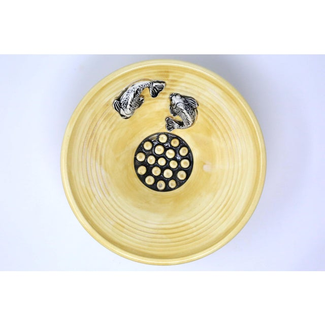 A handmade pottery ikebana vase, bowl or catch-all, with flared form, light ocher-colored glaze, and black/white sculpted...