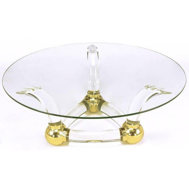 "Thick curved bar Lucite and brass ball fitments coffee table. Triangular base with three horn-shaped supports. 1/2"" thick..."