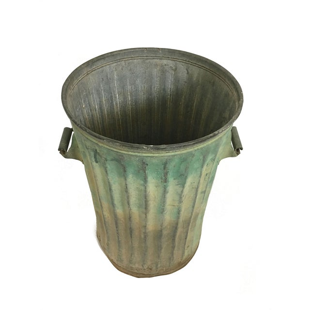 A vintage, green trash can with great patina.