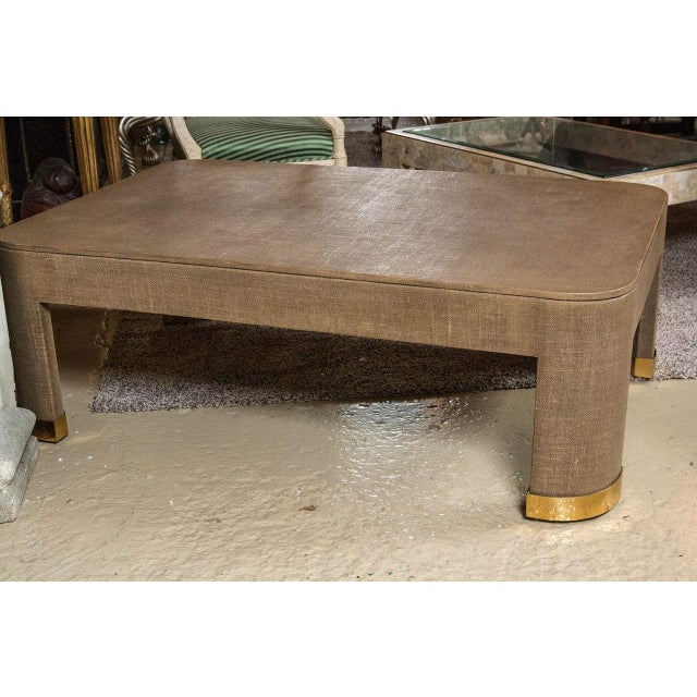 Heavy Parsons-style coffee table covered in a two-tone, camel-colored, lacquered linen with brass inlays. In the style of...