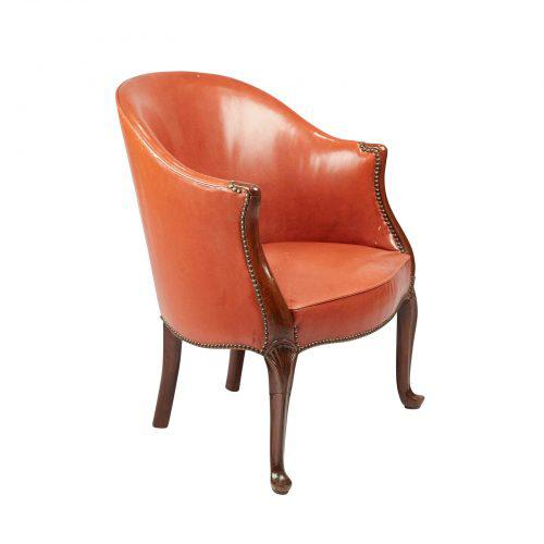 A George III English mahogany and leather desk chair – bergere in the French taste with subtle cabriole legs, circa 1780....
