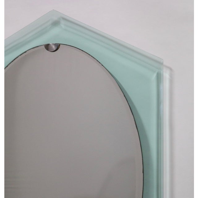 Italian midcentury mirror designed by Fontana Arte during the 1940s. The mirror is suspended on top of a clear/green...