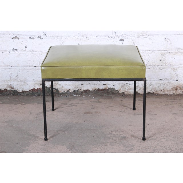 A stylish mid-century modern stool or ottoman designed by Paul McCobb. The stool features nice black iron legs with all...