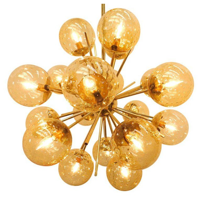 Italian chandelier shown in 18 amber Murano glass globes with carefully blown bubbles within the glass using Bollicine...