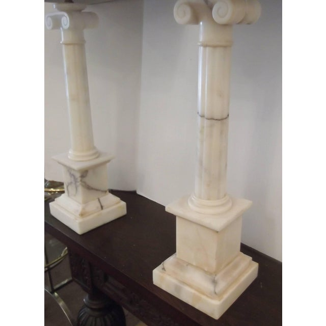 A handsome pair of Italian marble column lamps. Classic Ionic capitol topped columns with fluted center columns on plinth...
