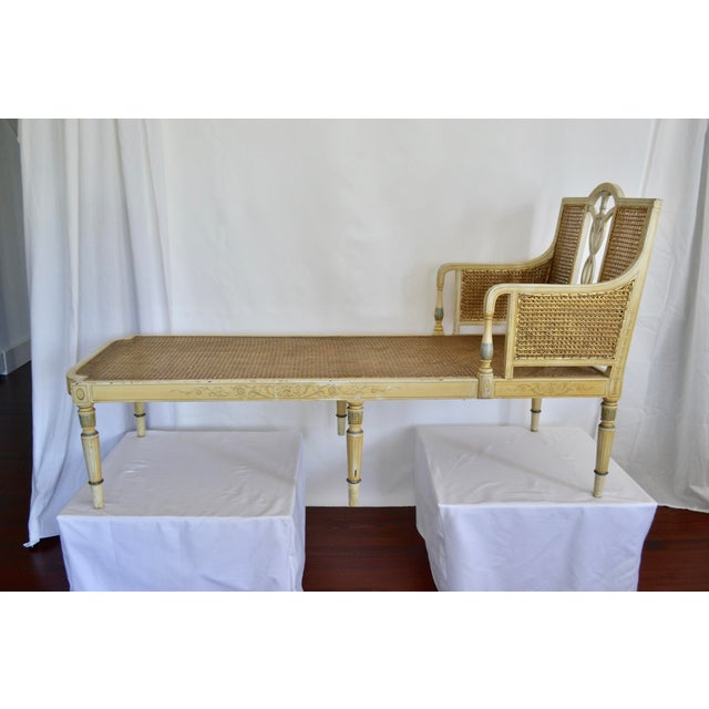 Featuring the original finish with original cane, this lovely paint decorated French revival chaise is from the early...