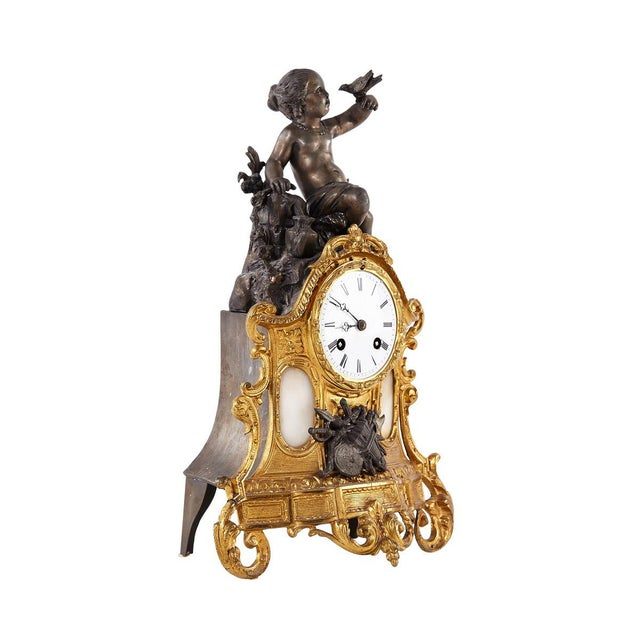 A mantel clock from the early part of the 1900's made in bronze with patinated metal and an alabaster in lay. White enamel...