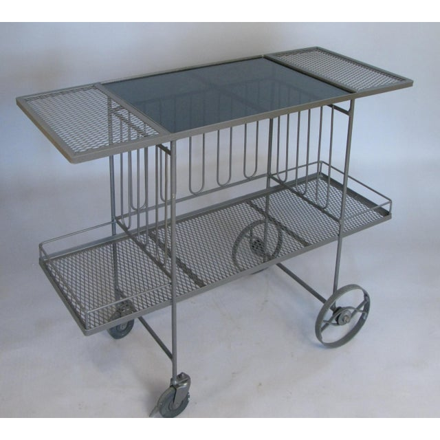 A very nice 1950s rolling bar cart in wrought iron with long vertical details around the center section, lower shelf with...