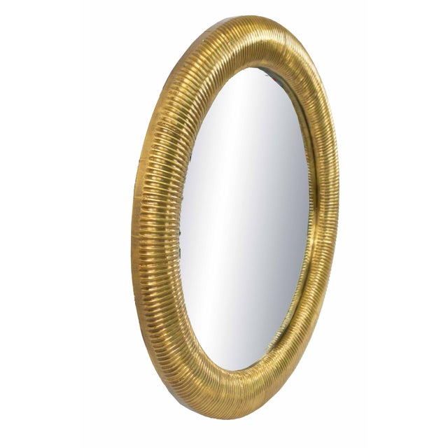 Contemporary round brass veneer framed beveled mirror with fluted design frame.