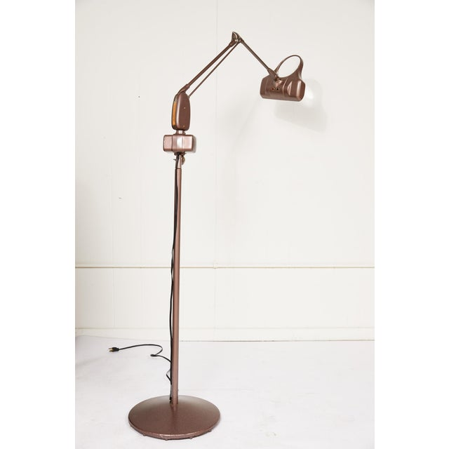 Midcentury industrial articulating single arm adjustable floor lamp with magnifier in an enamel finish by Dazor.