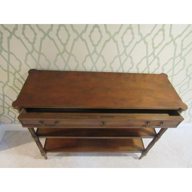 A console table by Baker Furniture. Four graceful fluted legs capped in solid bronze sabots. Its four legs also have a...