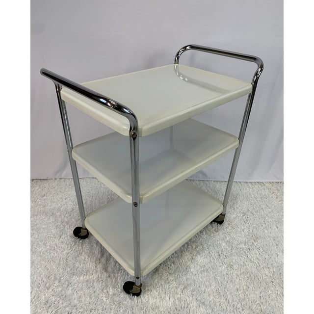 A 1950s vintage Midcentury Modern three-tier enameled metal rolling serving cart or bar cart by Cosco Hamilton. The...