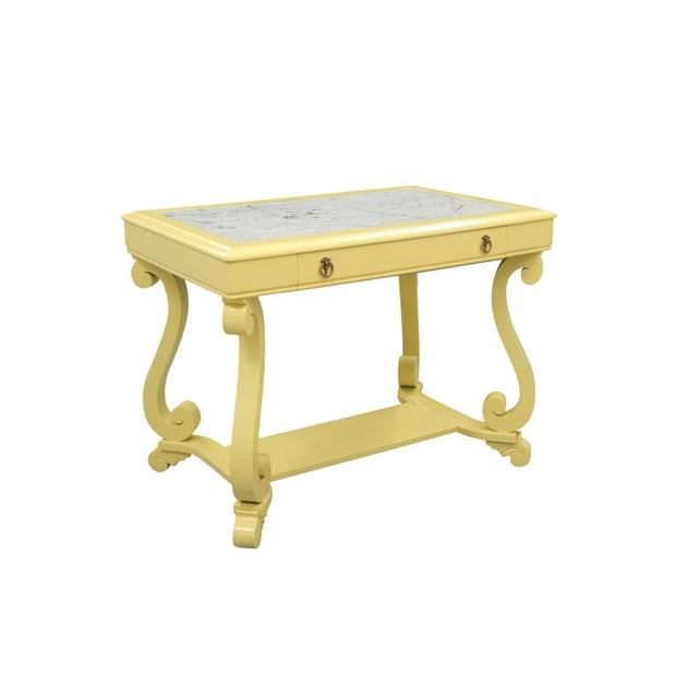 A Neoclassical style hall table. The top has an inset marble piece with rich grey veining throughout. A single drawer...